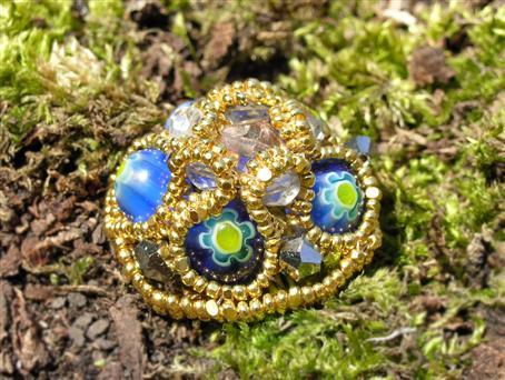 Бисер золотого цвета, и бусины с декоративным рисунком создают неповторимо роскошное сочетание увенчанное кристаллом...
